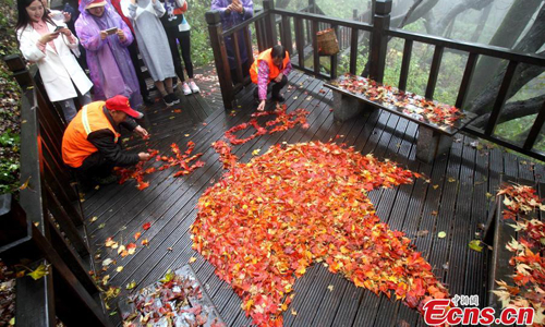 Sanitary workers form the Chinese phrase Yi Ye Zhi Qiu, meaning the falling of one leaf heralds the start of autumn, with leaves on Laojun Mountain in Luoyang, Central China's Henan Province, Oct. 15, 2016. Laojun Mountain is known for its cultural heritage relating to Taoism. It was once the retreat of Laozi, a great Chinese philosopher and the founder of Taoism. (Photo: China News Service/Wang Zhongju)