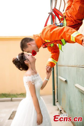 Firefighter Li Baogang and his wife pose for wedding photographs at a fire station in Xingtai City, North China's Hebei Province. Li descended from above with the help of cable, holding a flower in his mouth, to propose to his wife as his firefighting colleagues watched. (Photo: China News Service/Bai Leining)