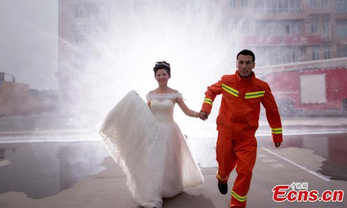 Firefighter Li Baogang and his wife pose for wedding photographs at a fire station in Xingtai City, North China's Hebei Province.(Photo: China News Service/Bai Leining)