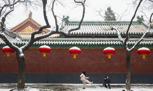File Photo: Two Beijing residents play in the snow on Nanchangjie Street in 2013. Photo: Li Hao/GT
