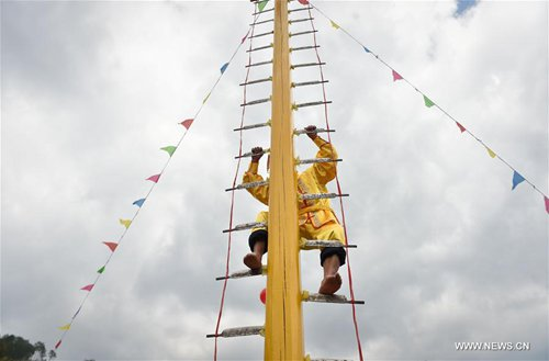 Villager Lan Ruzhu, 70, performs climbing on blades during a local folk activity held after harvest season in Zhongtuan Village of Wuping County, southeast China's Fujian Province, Nov. 14, 2016. The stunt, requiring a barefoot man climbing a ladder with 36 blades for rungs, has a history of several hundred years in western villages of Fujian. (Xinhua/Song Weiwei)