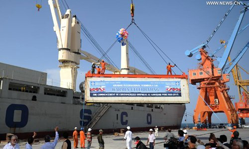 A container is loaded to a ship during the inaugration ceremony of container service at a pier of Gwadar Port, southwestern Pakistan, on May 11, 2015.Photo:Xinhua