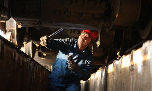 Cao checks the underside of a train with the help of a flashlight in Xuzhou, East China's Jiangsu Province on January 15, the third day of Chunyun. Photo: CFP