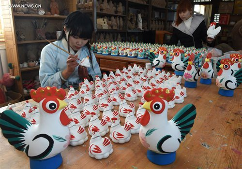 A girl paints a rooster-shaped clay sculpture in Botou, north China's Hebei Province, Jan. 20, 2017. Sculptures in the shape of rooster were made in Botou to meet the need for the Chinese lunar New Year - the Year of Rooster starting from Jan. 28 this year. (Xinhua/Fu Xinchun)