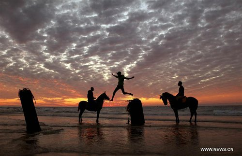 Palestinians enjoy themselves on the beach at sunset in Gaza City, Jan. 20, 2017. (Xinhua/Wissam Nassar)