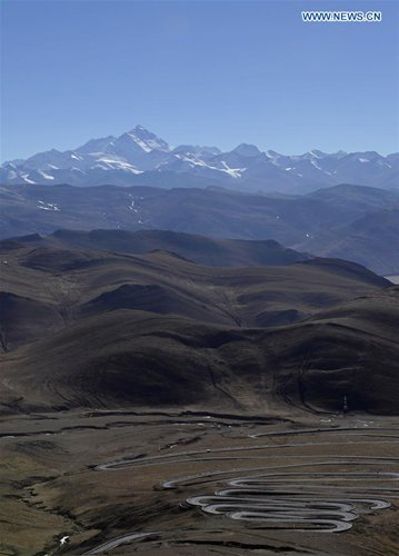 Photo taken on Dec. 23, 2016 shows mountain roads and Mount Qomolangma, southwest China's Tibet Autonomous Region. The 8,844.43-meter-high Mt. Qomolangma, located on the border of China and Nepal, is the world's tallest peak. (Xinhua/Liu Dongjun)
