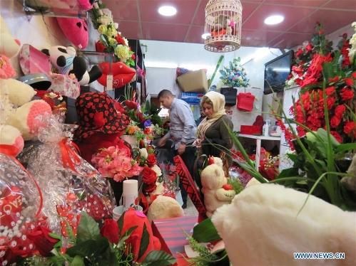 An Iraqi woman buys flowers at a gift shop ahead of Valentine's Day in Baghdad, Iraq, Feb. 13, 2017. (Xinhua/Khalil Dawood)