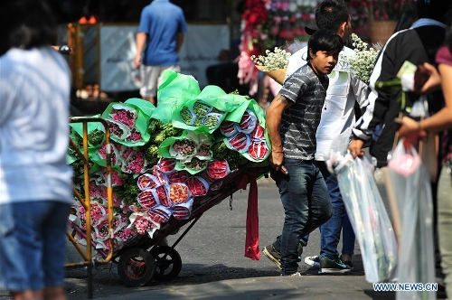 A worker delivers flowers ahead of the Valentine's Day at the Pak Klong Talad flower market in Bangkok, Thailand, Feb. 13, 2017. (Xinhua/Rachen Sageamsak)