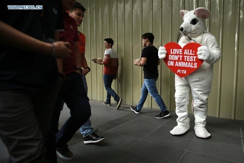 A member from PETA (People for the Ethical Treatment of Animals) dressed in a mouse costume holds a placard during a demonstration encouraging people to love all animals ahead of the Valentine's Day in Makati City, the Philippines, Feb. 13, 2017. (Xinhua/Rouelle Umali)
