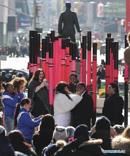 Patricia Falson (L, center) and Christopher Carter (R, center) attend their wedding during the Weddings in the Square Valentine's Day event at Times Square in New York, the United States, Feb. 14, 2017. Various activities such as Weddings in the Square, Surprise Proposal and Renewal of Vows were held for lovers to enjoy the Valentine's Day on Tuesday. (Xinhua/Wang Ying)