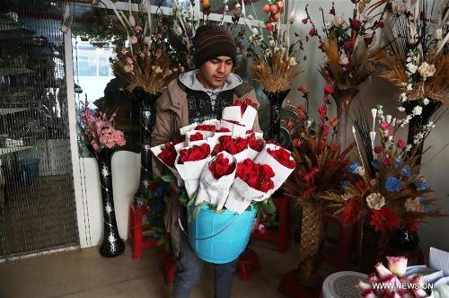 A shopkeeper carries flowers at his shop ahead of Valentine's Day in Kabul, capital of Afghanistan, Feb. 13, 2017. (Xinhua/Rahmat Alizadah)