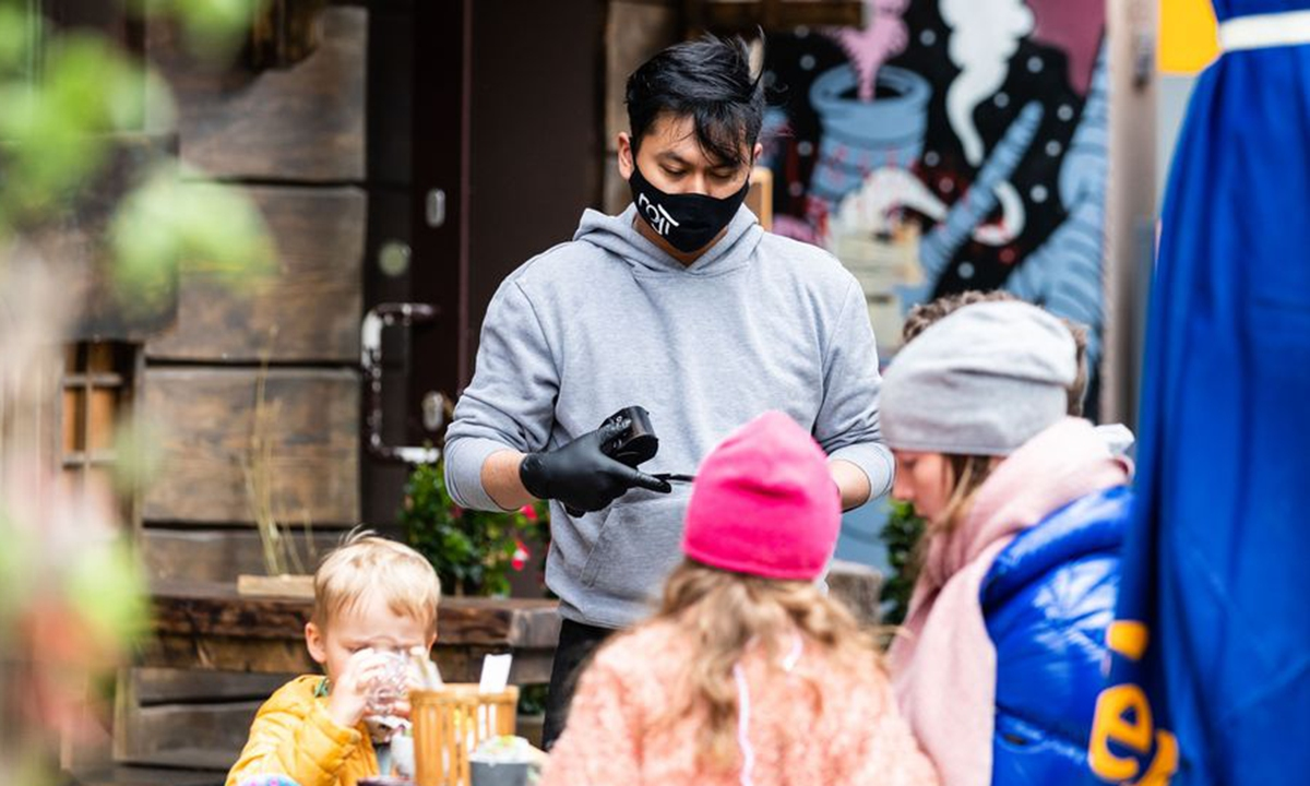 A waiter wearing a face mask serves customers at a reopened restaurant in Berlin, Germany, on May 16, 2020. (Photo by Binh Truong/Xinhua)