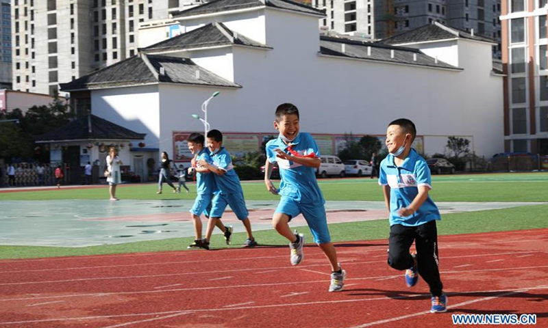 Pupils run on the playground at a primary school in Longnan City, northwest China's Gansu Province, Aug. 31, 2020. Some primary schools in Longnan, the city that was hit by flood recently, opened for the new semester on Monday. (Xinhua/Du Zheyu)