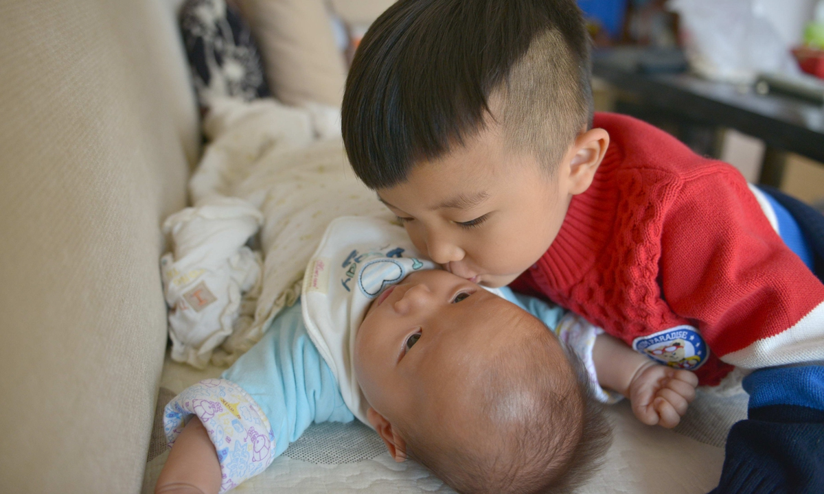 The older brother kisses his younger brother on his face in a family of two children in Guiyang, Southwest China's Guizhou Province. Photo: VCG