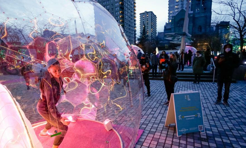 A dancer performs inside a bubble installation during the Dance Bubbles show at Wall Centre Plaza in downtown Vancouver, Canada, March 12, 2021. The show features large brightly-lit bubbles with dancers inside and provides physically distanced entertainment for residents. Photo: Xinhua