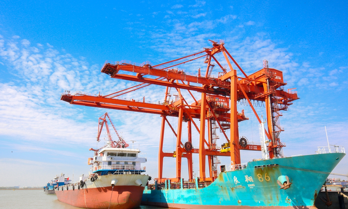 A cargo ship unloads goods at a port in Nantong, East China's Jiangsu Province on Monday. In the first quarter, container throughout at the port grew 51.9 percent year-on-year to 115,500 standard containers, and foreign trade container throughout soared 136.1 percent. Photo: CNSphoto