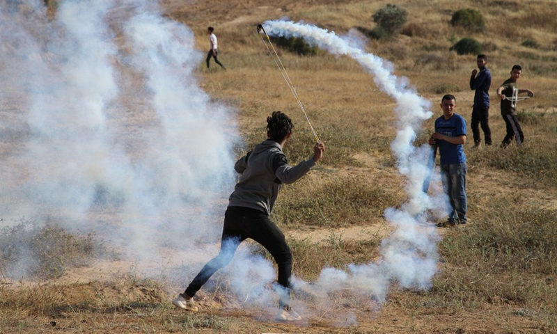 A Palestinian protester uses a slingshot to throw back a tear gas canister fired by Israeli troops during a protest against the violence in the Old City of Jerusalem, on the Gaza-Israel border, on May 8, 2021.(Photo: Xinhua)