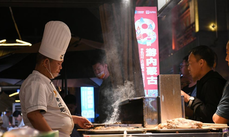 A cook grills lamb skewers in Hohhot, north China's Inner Mongolia Autonomous Region, June 10, 2021. Various activities such as appreciating traditional music and tasting local food are held here to promote tourism.   Photo: Xinhua