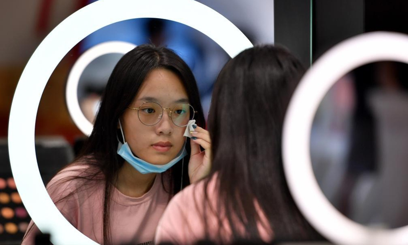 A customers tries a product at a duty-free shopping mall in Haikou, south China's Hainan Province, July 2, 2021. Official data shows that offshore duty-free sales in the province grew 226 percent between July 1, 2020 and June 30, 2021, reaching 46.8 billion yuan (about 7.2 billion U.S. dollars). Meanwhile, about 60.72 million items were sold to some 6.28 million customers.  Photo:Xinhua