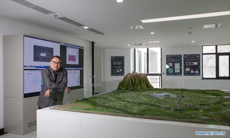 Gao Zhen, científico jefe del Gran Laboratorio de Ducha de Aire Alto de China (LHAASO), posó para una foto con la mesa de arena de LHAASO el 23 de febrero en el Instituto de Física de Altas Energías (IHEP) dependiente de la Academia China de Ciencias (CAS).  , 2021. Foto: Xinhua