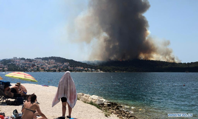 People look at a forest fire on a beach of the Island of Ciovo in Croatia, on July 10, 2021.(Photo: Xinhua)