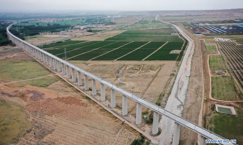 Aerial photo taken on July 10, 2021 shows part of the Zhongwei section of the Zhongwei-Lanzhou high-speed rail line in northwest China's Ningxia Hui Autonomous Region. A major high-speed railway in northwest China has entered a key phase recently, where the construction of overhead contact system has been rolled out.(Photo: Xinhua)