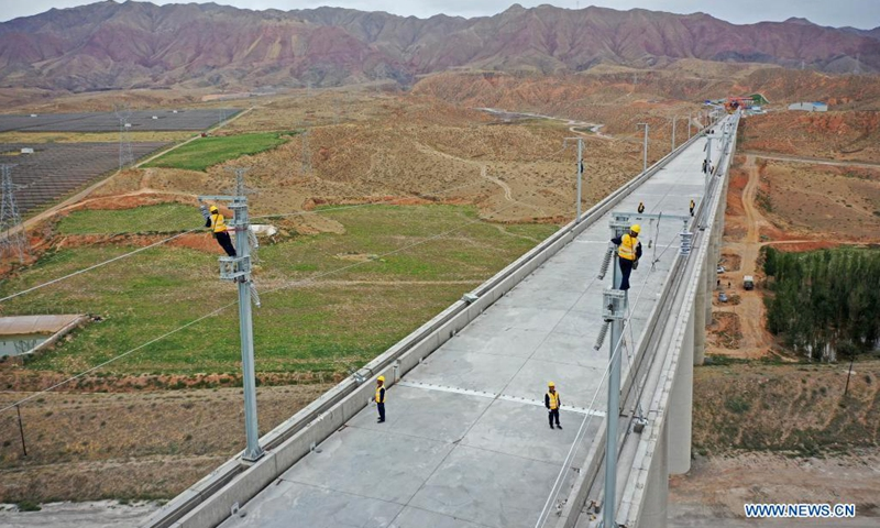 Aerial photo taken on July 10, 2021 shows railway staff members working at the Zhongwei section of the Zhongwei-Lanzhou high-speed rail line, in northwest China's Ningxia Hui Autonomous Region. A major high-speed railway in northwest China has entered a key phase recently, where the construction of overhead contact system has been rolled out.(Photo: Xinhua)