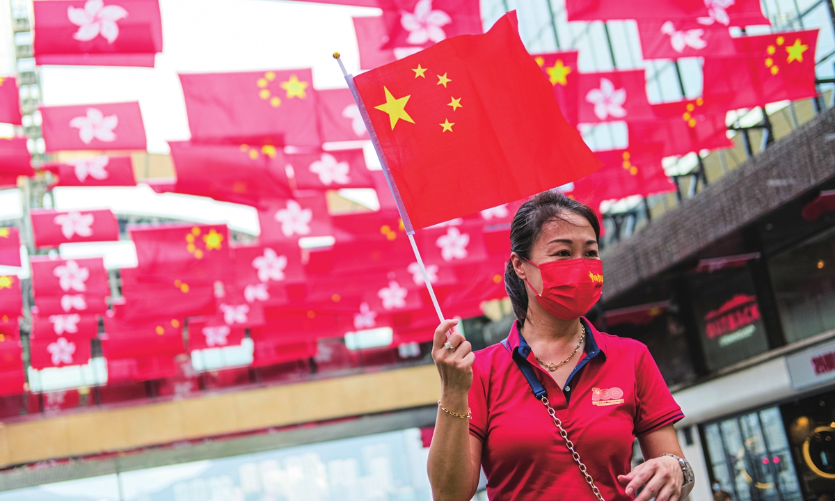 A woman holds a Chinese national flag and stands under the flags of China and Hong Kong SAR on July 1 to celebrate the 100th anniversary of the founding of the Chinese Communist Party and the 24th anniversary of Hong Kong return to China. Photo: IC