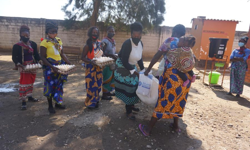 Beneficiaries of the food supplement program run by the Women's Federation for World Peace in Zambia hold received rations at a health facility in Lusaka, Zambia, on July 23, 2021.(Photo: Xinhua)