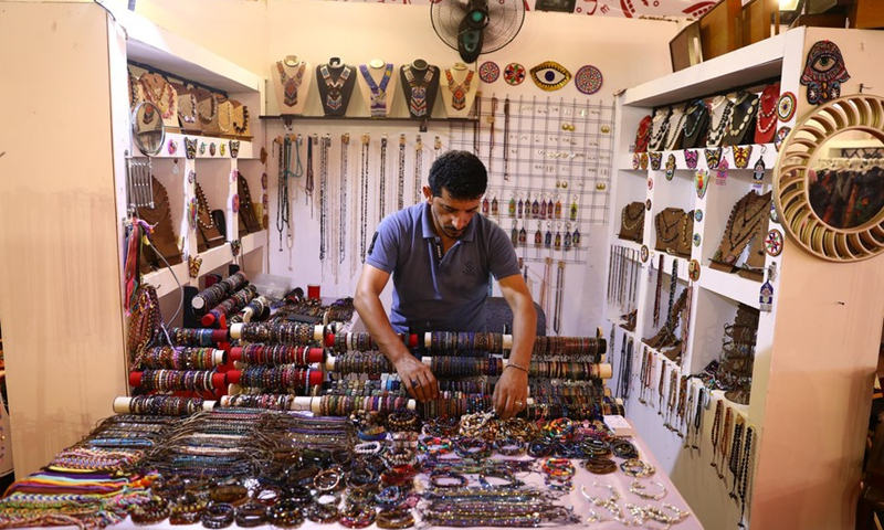 An exhibitor arranges his handicrafts during an annual exhibition for handicrafts in the resort city of New Alamein, Matrouh province, Egypt, on July 28, 2021.(Photo: Xinhua)