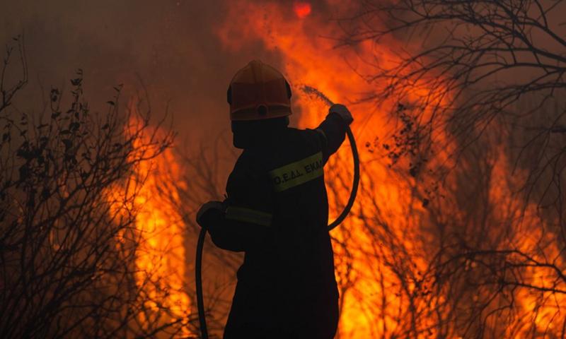 Ένας πυροσβέστης δίνει μάχη σε δασική πυρκαγιά στη Βαρυμπόμπη, Αχαρνές, Ελλάδα, 3 Αυγούστου 2021 (Φωτογραφία: Xinhua)