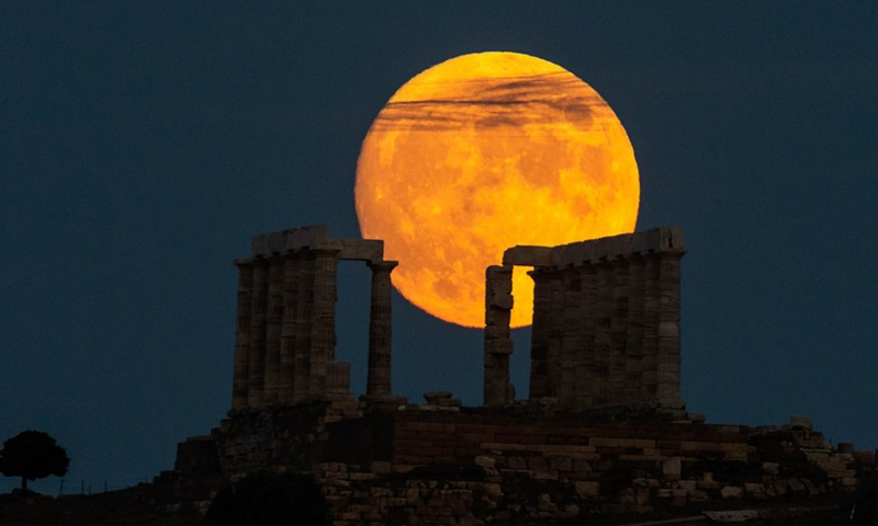 A full moon is seen over the Temple of Poseidon at cape Sounion, some 70 km southeast of Athens, Greece, on Aug. 21, 2021.(Photo: Xinhua)