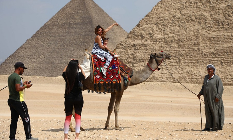 Two tourists riding a camel pose for photos in front of the Pyramids of Giza, Egypt, on Sept. 27, 2021.(Photo: Xinhua)