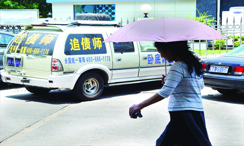 A woman passes by a vehicle with a debt collection ad and service telephone number on it. Photo: CFP