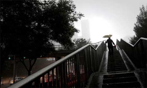 A pedestrian walks down an overbridge amid heavy rain in Beijing, capital of China, July 21, 2012. Photo: Xinhua