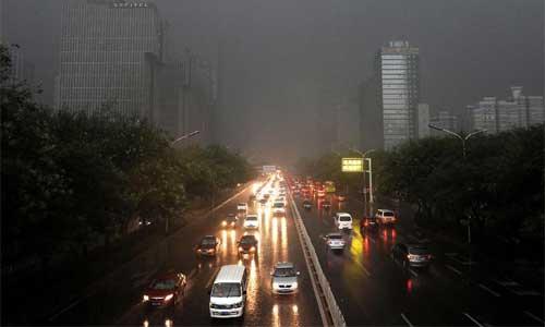 Vehicles turn on head lights while running amid heavy rain in Beijing, capital of China, July 21, 2012. Photo: Xinhua
