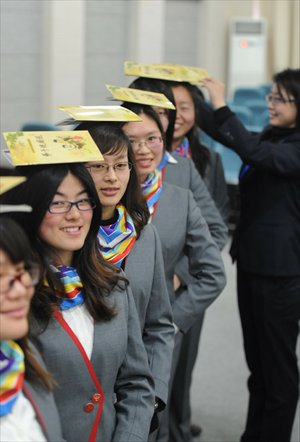 Young women at a finishing school in Yangzhou, Jiangsu Province, work on their posture and smiling on the eve of the 2012 International Women's Day. Photo: IC