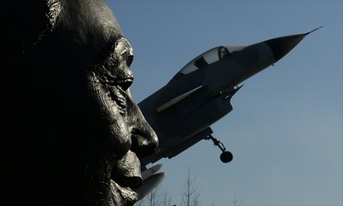 A statue of Wu Daguan (left), who is known as the father of China's military aviation industry, is displayed next to a Chinese produced J-10 fighter jet in Beijing on Thursday. Photo: AFP