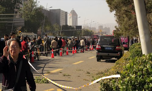 Pedestrians and vehicles draw along a street on Wednesday morning as police cordoned off the site of a series of explosions by homemade bombs near the provincial Party office buildings in Taiyuan, Shanxi Province. The blasts killed one and injured eight. Photo: IC