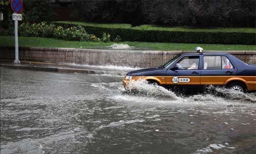 A taxi drives in heavy rain in Beijing, capital of China, July 21, 2012. Photo: Xinhua
