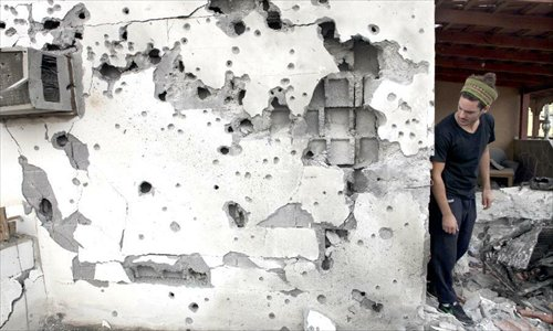 Ran Zohar, an Israeli resident, looks at his damaged house in Ofakim, south Israel, after being hit by a rocket fire from Gaza on November 19, 2012. Photo: Xinhua