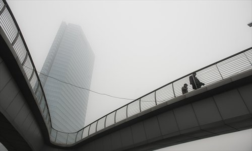 A building is obscured by smog in Beijing, the capital of China, on January 29, 2013. The National Meteorological Center (NMC) issued a code-blue alert on January 27 as the smoggy weather forecast for the following two days would cut visibility and worsen air pollution in some central and eastern Chinese cities. Photo: Li Hao/GT