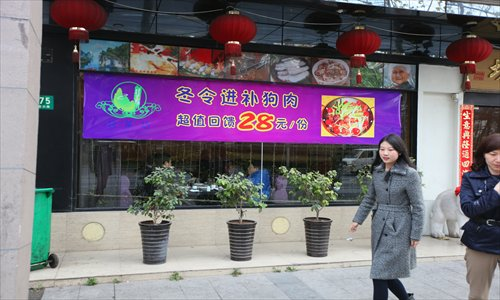 A woman passes by a restaurant in Xuhui district advertising a dog meat dish for 28 yuan. Photo: Cai Xianmin/GT