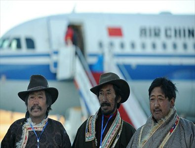 Staff members pose for group photos in front of the test flight at the Daochengyading Airport in Daocheng County of the Tibetan Autonomous Prefecture of Garze, southwest China's Sichuan Province, November 23, 2012. The first test flight of the airport successfully landed Friday. With the height of 4,411 meters above sea level, the Daochengyading Airport becomes the highest civil airport in the world. (Xinhua/Xue Yubin)