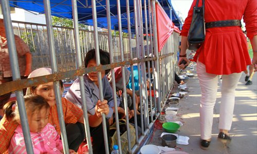A visitor passes by beggars who are segregated behind bars at a Buddhist temple fair in Jiangxi Province. Photo: CFP
