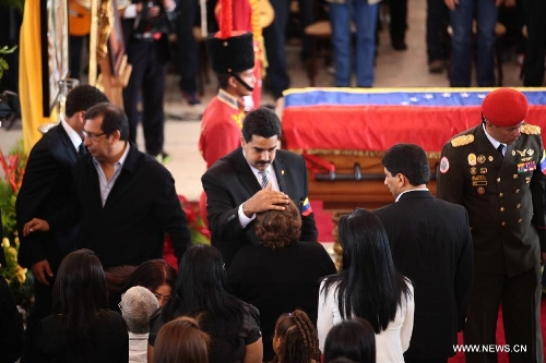 Elena Frias (C) receives condolences from Venezuela's President Nicolas Maduro (C L) in front of the body of late Venezuelan President Hugo Chavez during a honor ceremony at the Military Academy's fire chapell, prior to his carrying from the Military Academy to the Mountain Barracks, in the city of Caracas, capital of Venezuela, on March 15, 2013. Hundreds of thousands of Venezuelans Friday marched alongside the casket of their late President Hugo Chavez, as his remains were taken to the mountaintop barracks he once called home and today houses the Historic Military Museum. (Xinhua/AVN)