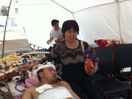 A mother who saved her son by moving away a slab weighing over 50 kilograms alone in the earthquake, looks after her son at a temporary treatment tent. Photo: West China City Daily