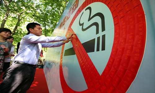 A man signs his name at an anti-smoking campaign event. Photo: CFP