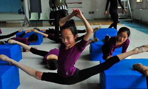 A girl stretches at the Shenyang Sports School in Liaoning Province.