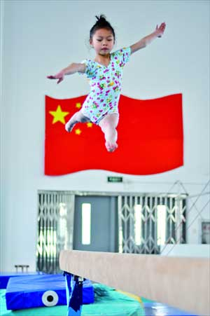 A young gymnast leaps from the balance beam. Photo: Cai Xianmin/GT